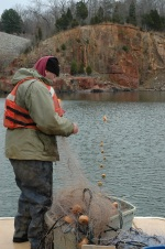 A research technician with the Georgia Unit deploys a gill net as part of a research project